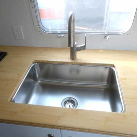 You're looking at a stainless steel sink with Grohl faucet and bamboo countertops in this 1985 Excella Airstream.
